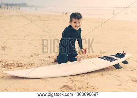 Adorable Child Waxing Surfboard On Beach. Cute Happy Little Boy In Wetsuit Kneeling On Sand And Waxi