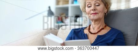Portrait Of Adult Woman Reading Interesting Book. Aged Curly-haired Grandmother Sitting On Sofa At H