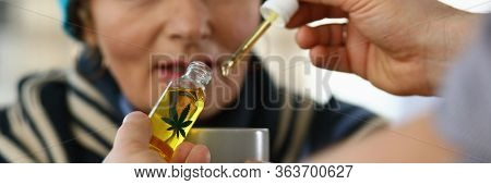 Focus On Male Hand Holding Bottle With Cannabinoid Oil At Hospital. Professional Practitioner Giving