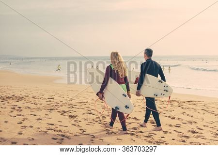 Back View Of Couple With Surfboards Walking On Beach. Rear View Of Man And Woman In Wetsuits Holding