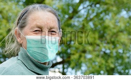 Smiling Elderly Village Grandmother Wearing Medical Protective Mask Outdoors. Prevention During Coro