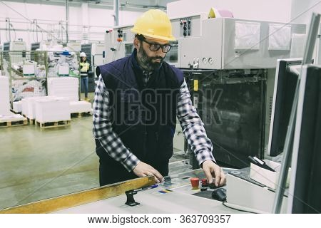 Focused Male Factory Worker Operating Machine At Control Panel. Bearded Middle Aged Man In Hardhat W