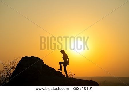 Silhouette Of A Woman Hiker Climbing Up A Big Stone At Sunset In Mountains. Female Tourist On High R