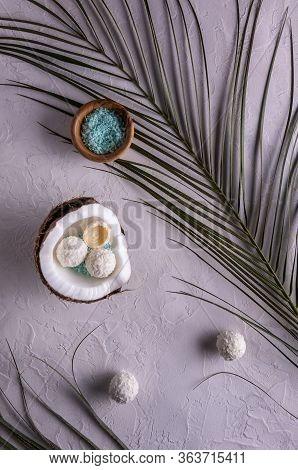 Flat Lay With Half Of Coconut In Shell, Coconut Flakes In Bowl, Coconut Candies And Palm Leaves On W