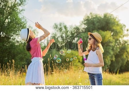 Children Two Girls Blowing Soap Bubbles. Beautiful Natural Landscape, Summer Meadow Background, Happ