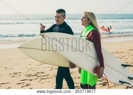 Middle Aged Couple With Surfboards Walking On Beach. Side View Of Man And Woman In Wetsuits Holding