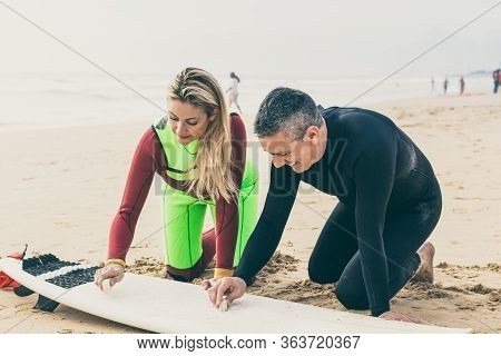 Happy Couple Waxing Surfboard On Beach. Cheerful Man And Woman In Wetsuits Sitting On Sand And Waxin