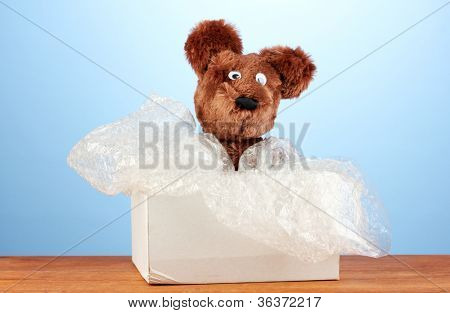 Opened parcel with a child's toy on blue background close-up