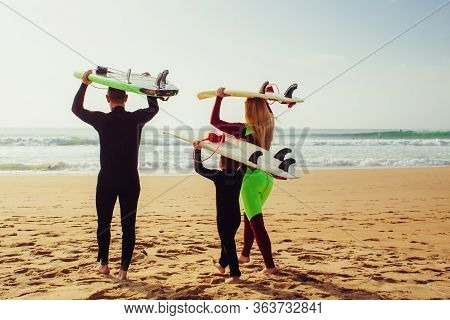Family With Surfboards Walking On Beach. Back View Of Parents With Cute Little Son In Wetsuits Holdi