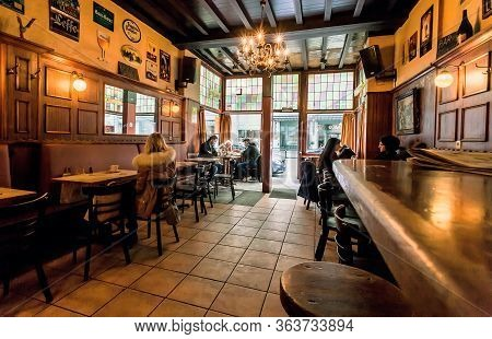 Brussels, Belgium: Not Many Bar Visitors Having Lunch Inside The Old-style Interior With Wide Window