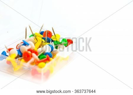 Plastic Box With Multi-colored Pushpins On The White Background. Side View With Selective Focus.