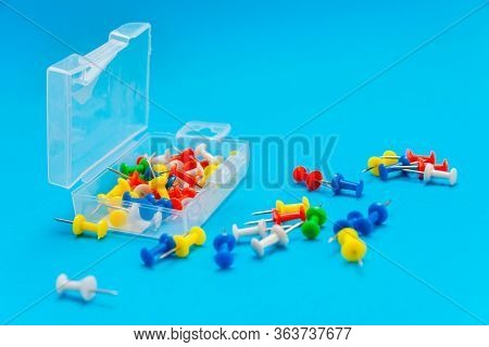 Plastic Box With Multi-colored Pushpins On The Blue Background. Some Of The Pins Scattered Around. S