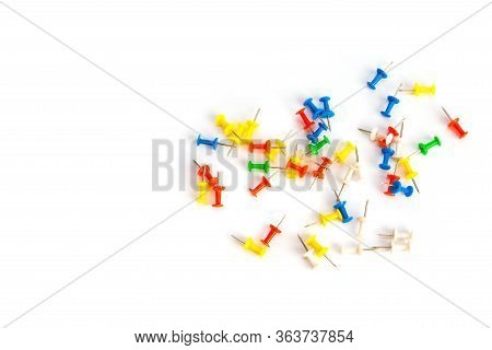 Multi-colored Pushpins Scattered Over A White Background. Top View With Copy Space