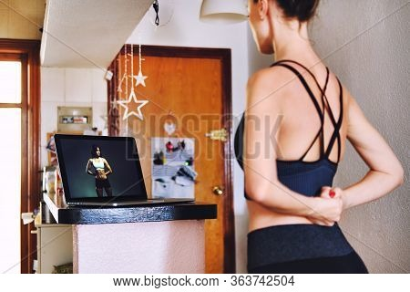 Rearview Woman Working Out At Domestic Home Kitchen Using Computer On-line Training, Pc Screen View