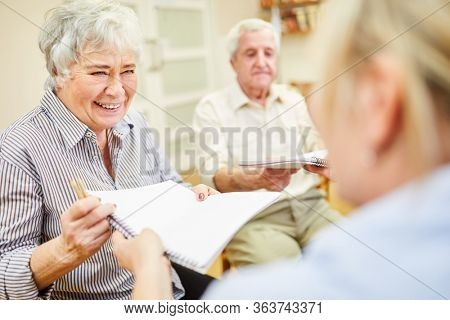 Cheerful senior woman and therapist in creative painting therapy with drawing pad