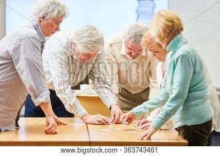 Group of seniors with dementia playing the puzzle as memory training in a retirement home