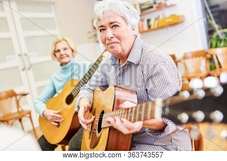 Senior woman learns to play guitar in a guitar course at the adult education center