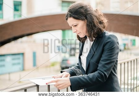 Focused Businesswoman Reading Papers On Street. Concentrated Middle Aged Businesswoman In Formal Wea