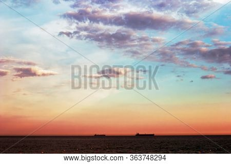 The Black Sea With A Fabulous Sky From Blue To Red. Two Ships On The Horizon. Beach Area Marked With