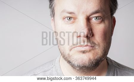 Mid Adult Man Looking At Camera - Close Crop Headshot With Copy Space On Gray Background