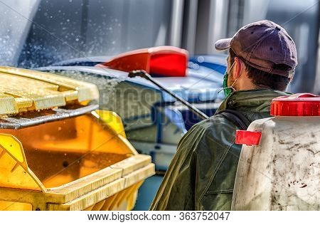 Spraying And Disinfecting Trash Cans By Man Due Coronavirus Covid-19