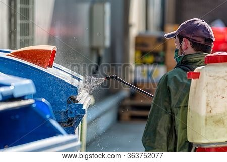 Man In Protective Suit Disinfects And Spraing Public Places.