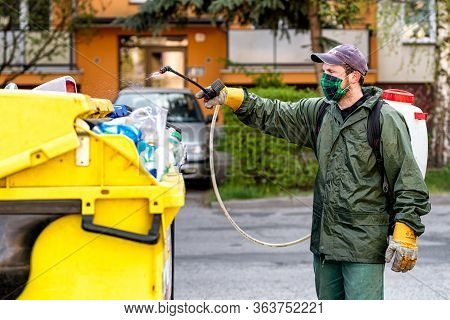 Ruzomberok, Slovakia - April 29, 2020: Man In Protective Suit Disinfects With A Sprayer In The City.