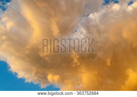 Sunset sky background. Picturesque colorful golden clouds lit by evening soft sunlight. Vast sky landscape panoramic scene - colorful sunset sky view. Blue sky background. Picturesque colorful sky clouds lit by sunlight. Vast sky landscape panoramic scene