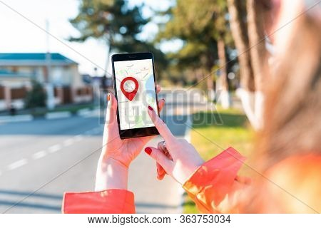 A Womans Hand Holds A Smartphone With An Online Map That Has A Red Geolocation Icon On It. In The Ba