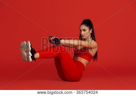 Abs. Beautiful Young Female Athlete Practicing In Studio, Monochrome Red Portrait. Sportive Fit Brun