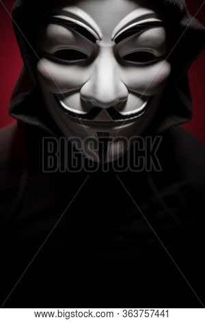 St. Petersburg - Russia - 25 December 2019 - Anonymous Person In Guy Fawkes Mask On Black Background