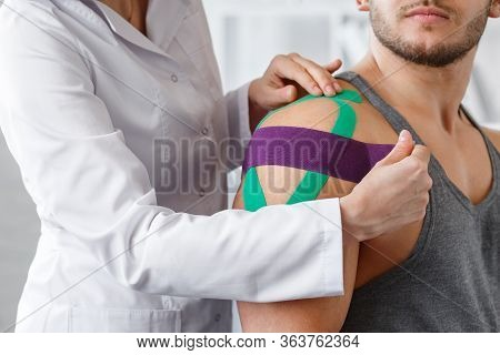 Kinesiology Taping. Physical Therapist Applying Kinesiology Tape To Patient Shoulder. Female Therapi