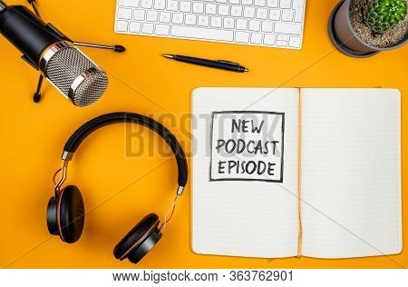 Top View Of Text New Podcast Episode On Notepad On Desk With Microphone, Computer Keyboard And Headp