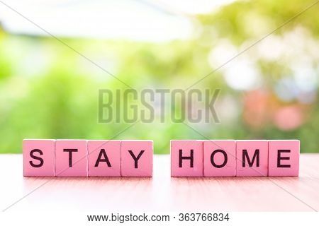 The Stay Home Word Written On Pink Color Wood Block On Wooden And Nature Background, Covid-19 Concep