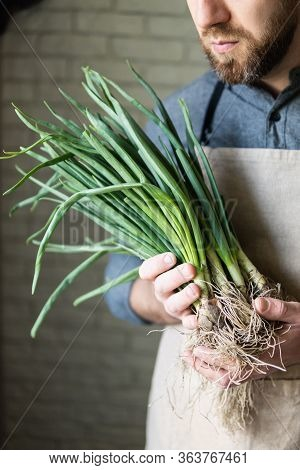 Young Man In Rustic Apron Holding A Bunch Of Green Onions