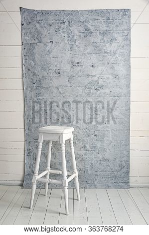 White High Bar Chair With Grey Textured Background. High Bar Chair On White Floor. White High Bench