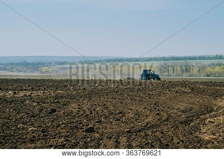 Tractor Plows A Field In The Spring Accompanied By Rooks Tractor . Far View . Time To Plow Concept .