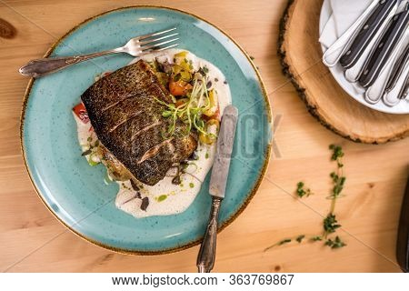 Grilled Salmon And Vegetables And Sauce On Blue Plate