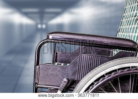 Empty Wheelchair In Hallway Of Hospital Or Retirement Nursing Care Home With Copy Space. Concept Of