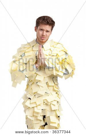 The young man covered with yellow sticky notes, isolated on white background