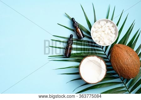 Aromatherapy Massage Coconut Oil With Sliced Coconut In Bowl, Half Of Coconut, Tropical Palm Leaf On