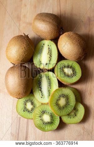 Fresh Juicy Kiwi Fruits Closeup. Whole And Cut Half Of Kiwifruits On Wooden Chopping Board Or Table.