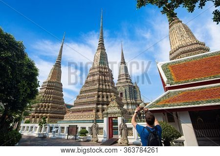 Tourist Man With Camera Take Photo View Of Thai Ancient Artistic Architecture Pagoda In Wat Poh, Loc