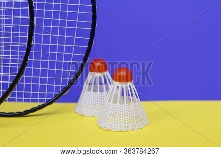 Badminton. Three Shuttlecocks And Two Badminton Rackets. Colored Yellow Background. Idea For A Magaz