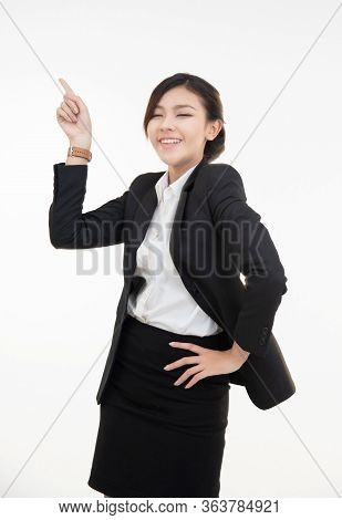 Attractive Young Asian Businesswoman Looking At Camera, Showing Finger Up At Workplace,likes Her Job