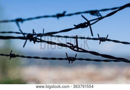 Closeup Of A Barbed Wire Against Blue Sky