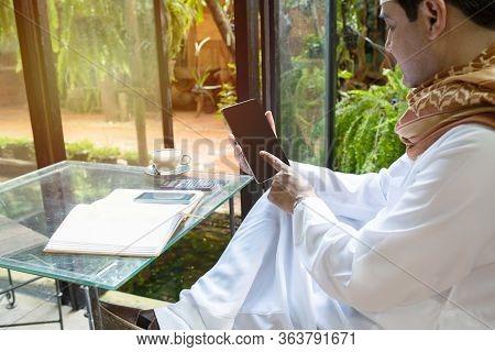Pakistani Business Asian Man Using Tablet,sitting In Green Cafe Wear Muslim Dress,freelance Business