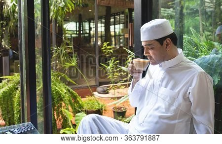 Asian Mid Aged Muslim Business Man Sit In Coffee Shop Drink Coffee