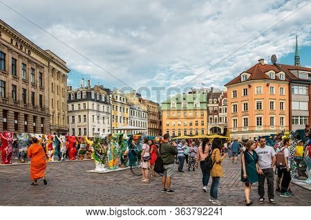 Riga, Latvia - July 12, 2018: People Walk Around Dome Square And Look At The Sculptures Of The Inter