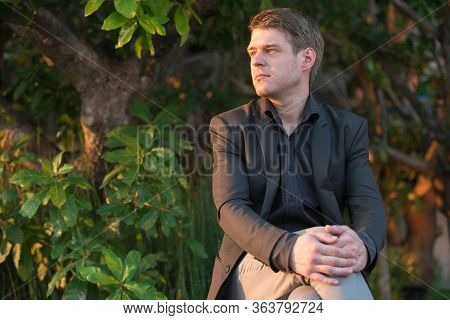 Young Handsome Businessman In Suit Sitting In Nature Outdoors